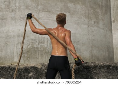 Fit young man with rope on grey background. Healthy adult man from behind.