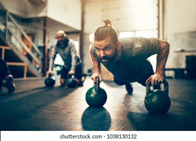 Fit young man in sportswear doing pushups with dumbbells during a workout session at the gym