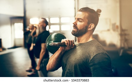 Fit young man in sportswear holding a dumbbell during a workout class in a gym