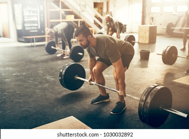Fit young man in sportswear preparing to lift weights during an workout session in a gym
