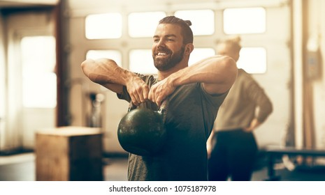 Fit young man in sportswear smiling and lifting dumbells during an exercise class in a gym