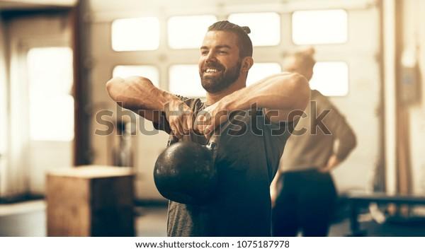 スポーツウェアを着た若い男性は体育館での運動教室で、笑顔でダンベルを持ち上げる