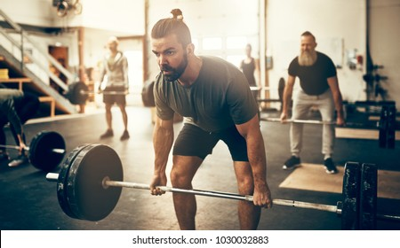 Fit young man in sportswear straining to lift heavy weights during a workout session in a gym