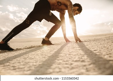 Fit young man in starting position ready for running. Athlete ready to start a race over desert sand with sun shining in background.