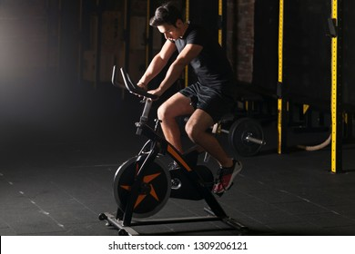 Fit young man using exercise bike at the gym.