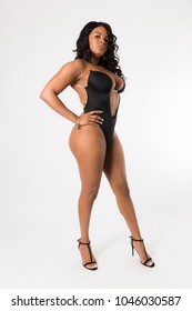 Fit young mixed race woman with long curly hair poses in a black two piece against a white background