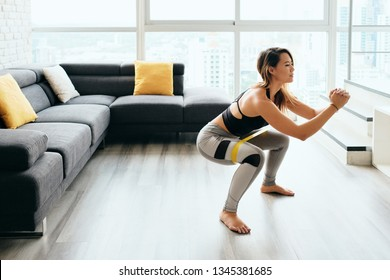 Fit young Pacific Islander woman training at home. Beautiful female athlete working out for wellbeing in domestic gym, training legs muscles doing side to side squats with elastic band.