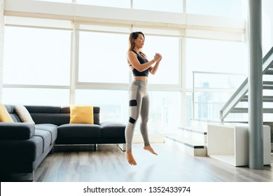 Fit young Pacific Islander woman training at home. Beautiful female athlete working out for wellbeing in domestic gym, training legs muscles with squats and jumps.