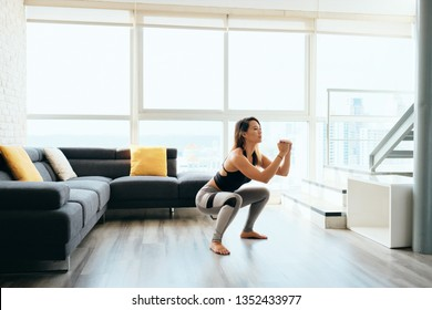 Fit young Pacific Islander woman training at home. Beautiful female athlete working out for wellbeing in domestic gym, training legs muscles with in and out squats.