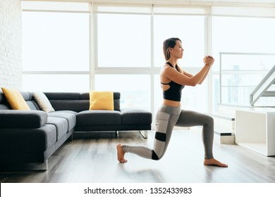 Fit young Pacific Islander woman training at home. Beautiful female athlete working out for wellbeing in domestic gym, training legs muscles doing lunges exercise