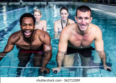 Fit young people cycling in the pool