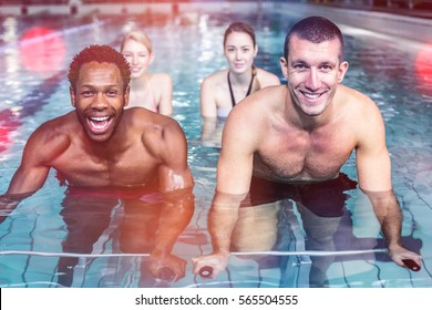 Fit young people cycling in pool