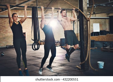 Fit young people doing pullups looking determined, working out in a gym