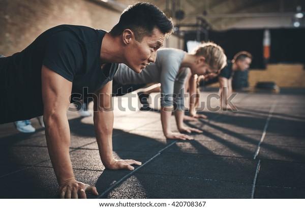 Jóvenes acomodados haciendo títeres en un gimnasio enfocado