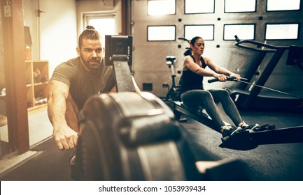Fit young people exercising together on rowing machines during a workout session in a gym
