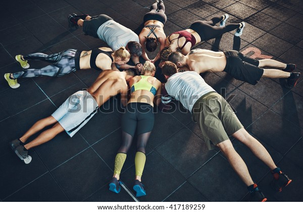 Fit young people focused on planking in a circle in a gym