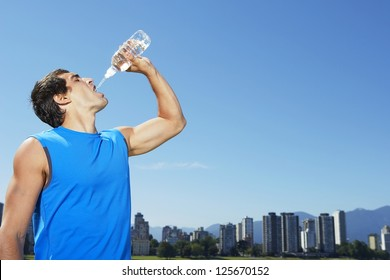 Fit young sportsman with his head back drinking water from a plastic bottle with an urban cityscape in the distance