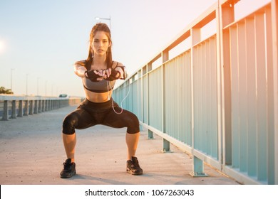 Fit young sporty girl doing squats outdoors.