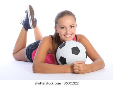 Fit young teenage athlete girl lying on the floor holding soccer ball with beautiful smile wearing pink vest and denim shorts. Full body shot against white background.