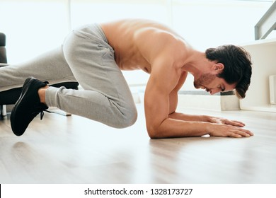 Fit young white man training at home. Handsome hispanic male athlete working out for wellbeing in domestic gym, training abdomen and legs muscles with mountain climbing plank