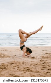 Fit young woman in bikini doing balance yoga exersice at the beach. Outdoor fitness and healthy lifestyle.
