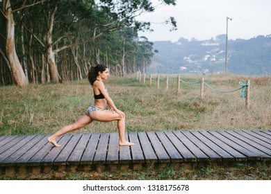 Fit young woman in bikini doing stretching warm up exersice or lunges at the beach. Outdoor fitness and healthy lifestyle.