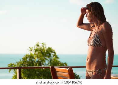 Fit young woman in a bikini looking into the sunset, tan skin with shining drops of water