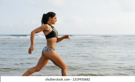 Fit young woman in bikini running at the beach. Outdoor fitness and healthy lifestyle.