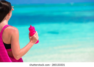 Fit young woman with bottle on tropical white beach in her sportswear