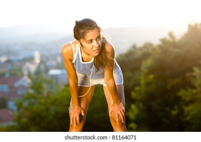 Fit young woman catching her breath during training