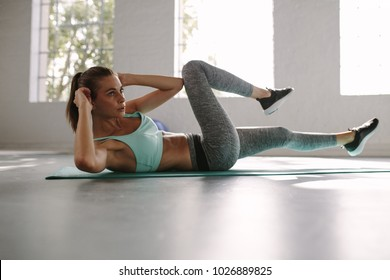 Fit young woman doing bicycle crunch workout to improve her abs. Female in the gym doing sit-up exercise.