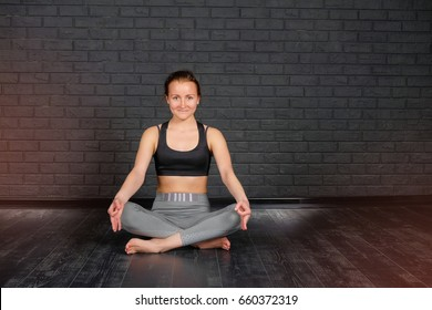 A fit young woman doing the lotus pose in yoga class against a gray brick wall. Relaxation and Stretching. Healthy lifestyle. Woman do yoga in fitness studio.