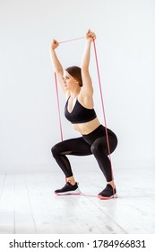 Fit young woman doing a power band squat overhead resistance exercise to strengthen and tone her muscles in a high key gym in a health and fitness concept