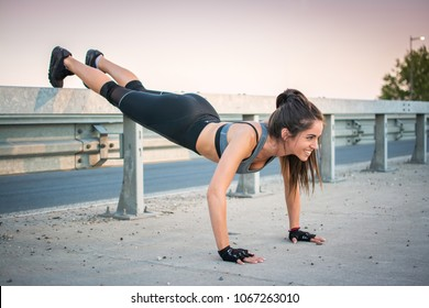 Fit young woman doing push ups over bridge's fence during evening training outdoors.