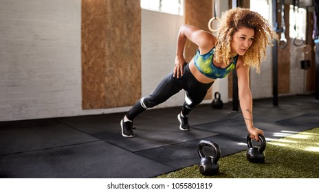 Fit young woman doing pushups with dumbbells alone on a gym floor during a workout session