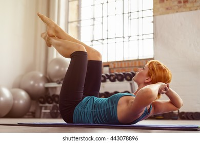Fit young woman doing sit ups and leg raisers on a mat in the gym to strengthen her abdominal muscles in a healthy lifestyle concept