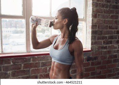 Fit young woman drinking water in the gym. Muscular woman taking break after exercise.