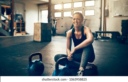 Fit young woman in exercise gear smiling while sitting alone on the floor of a gym after a workout
