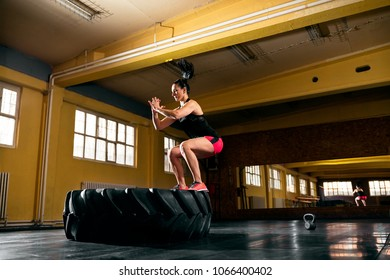 Fit young woman exercising at gym, jump high to big tire at gym