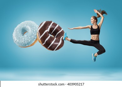 Fit young woman fighting off bad food on a blue background