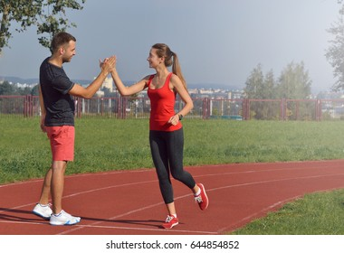 Fit young woman giving high five to her boyfriend after a run. Healthy fitness concept with active lifestyle.