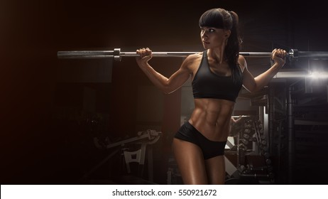 Fit young woman in great shape lifting barbells looking focused, working out in a gym. Sport, bodybuilding, lifestyle concept Sporty sexy woman doing squat workout Strong legs Wide 16 x 9 picture