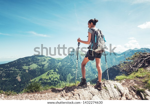 Fit young woman hiking in the mountains standing on a rocky summit ridge with backpack and pole looking out over an alpine landscape