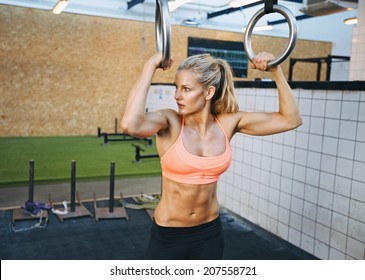 Fit young woman holding gymnast rings at the gym looking away. Young caucasian woman exercising at gym.
