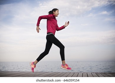 Fit young woman jogging beside the sea