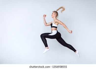 Fit young woman jumping against grey background. Female model in sports wear jumping. Dynamic movement.