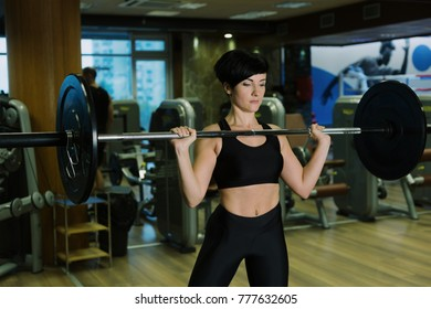 Fit young woman lifting barbells looking focused, working out in a gym, doing barbell push press
