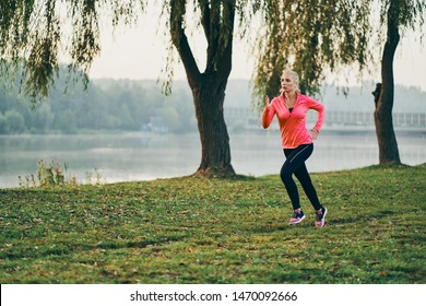 Fit young woman listening to music and jogging near lake on sunny autumn morning