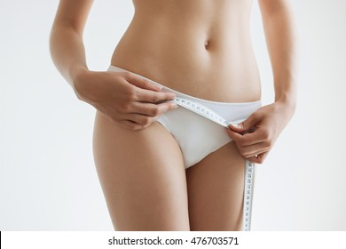fit young woman measuring her waistline, grey blurred background with a space for your text.
