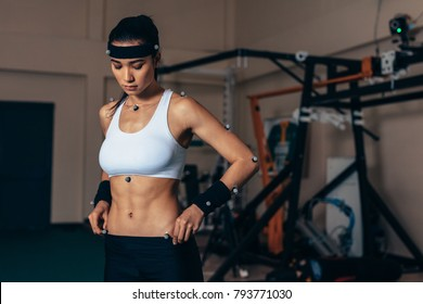 Fit young woman with motion capture sensors on her body in sports lab. Female athlete testing her performance in biomechanics lab.